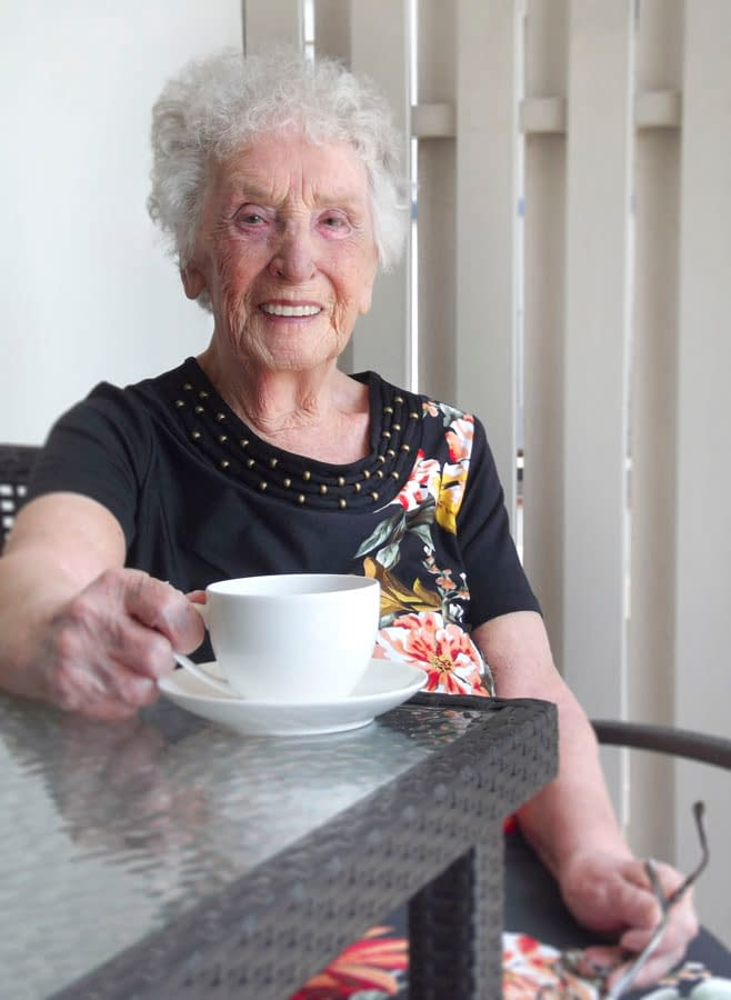 Smiling elderly lady drinking coffee on a patio outside her home