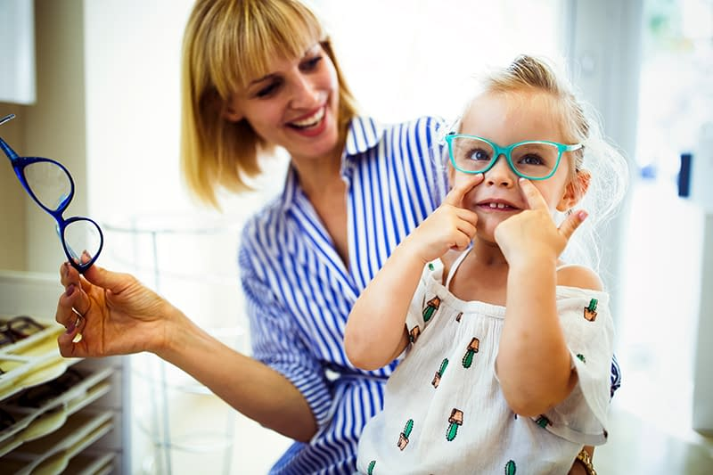 Happy mother with her little daughter choosing glasses