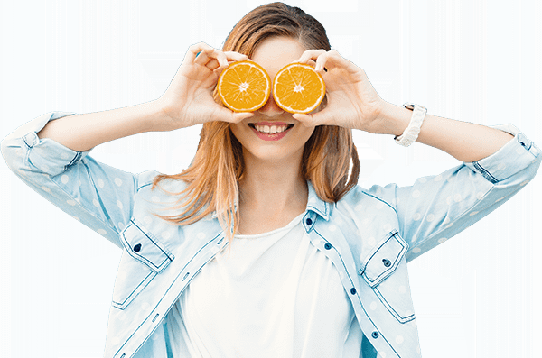 Woman posing holding orange slices in front of her eyes